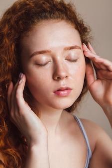 아름다운 redhaired 소녀는 그녀의 얼굴을 씻고 그녀의 눈을 감았다 십대 피부 관리 개념 메이크업 클로즈업 없이 베이지색 배경에 스튜디오에서 샷