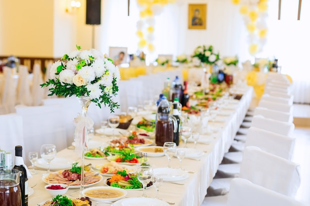 맛있는 요리와 음료가 가득하고 섬세한 부케가 달린 크고 얇은 꽃병이있는 결혼식 손님을위한 테이블이있는 아름다운 레스토랑 홀