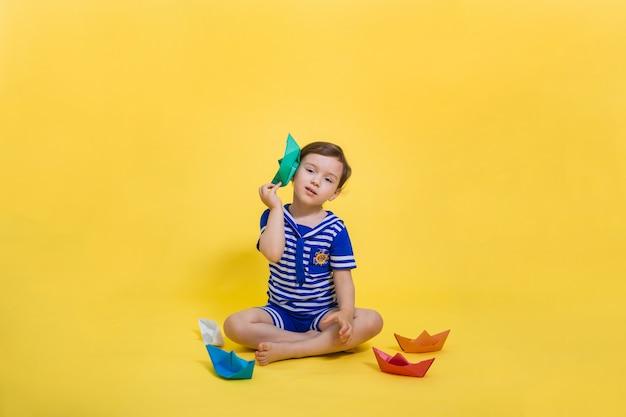 紙の船を手にした美しいセーラー少女が黄色のスペースに座って見える。黄色いスペースの空きスペース。紙折り紙。