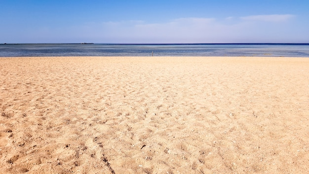 Красивый песчаный пляж без людей и тропическое синее море на фоне голубого неба.