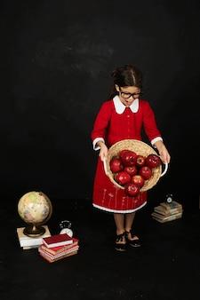 本りんごと黒の背景に地球と赤いドレスの美しい女子高生
