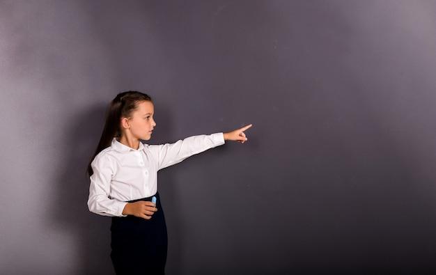 교복을 입은 아름다운 여학생이 텍스트를 위한 장소가 있는 검정색 배경에 손을 대고 가리키고 있다