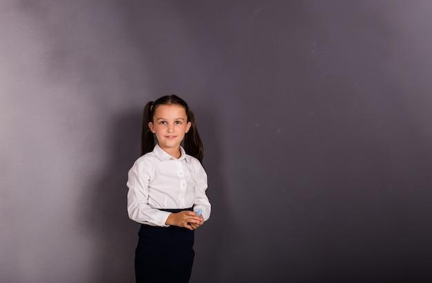 Красивая школьница в форме стоит на черном фоне с местом для текста