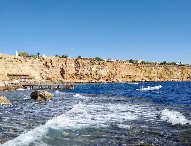 岩とホテルのある美しい海辺。