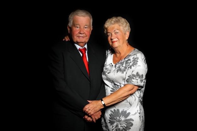 Красивая старшая пара стоя вместе на черном фоне