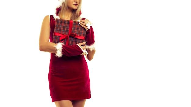 新年のドレスを着た美しいセクシーな女の子は、手に贈り物を持っています。クリスマスや新年のお祝い