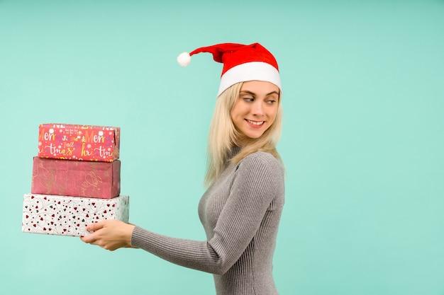 Красивая сексуальная девушка в новогодней шапке и сером платье, держит в руках подарки празднование рождества или нового года на синем фоне