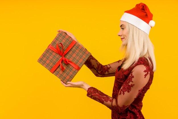새해 모자와 회색 드레스에 아름다운 섹시한 여자, 손에 선물을 잡아