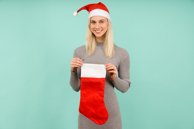 새해 모자와 회색 드레스를 입은 아름다운 섹시한 소녀가 크리스마스 양말을 들고 있습니다. 크리스마스 또는 새해 축하-이미지