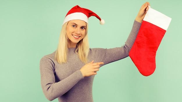 新年の帽子と灰色のドレスを着た美しいセクシーな女の子は、クリスマスの靴下に指を指しています。クリスマスや新年のお祝い
