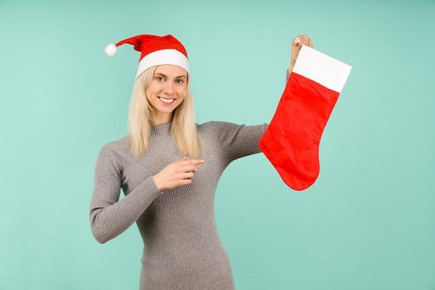 새해 모자와 회색 드레스를 입은 아름다운 섹시한 여자가 크리스마스 양말에 손가락을 가리 킵니다.