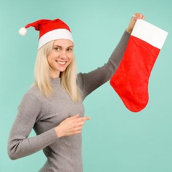 Красивая сексуальная девушка в новогодней шапке и сером платье показывает пальцем на рождественский носок