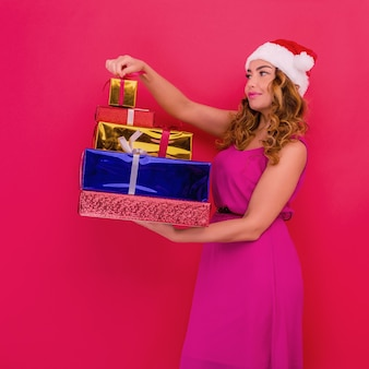 新年の帽子をかぶった美しいセクシーな女の子は、手に贈り物を持っています。クリスマスや新年のお祝い