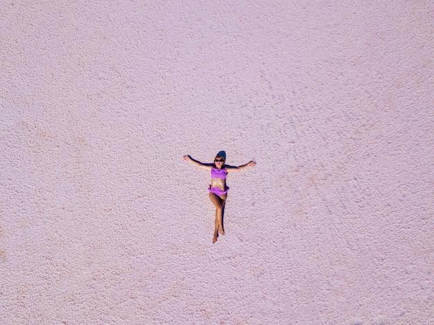 ピンクの塩湖でポーズをとるピンクの水着姿の美しいセクシーな女の子。塩辛いピンクの湖で日焼けした女の子の写真撮影。