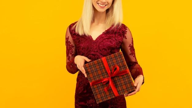 赤いドレスを着た美しいセクシーな女の子は、贈り物を手に持っています。クリスマスや新年のお祝い