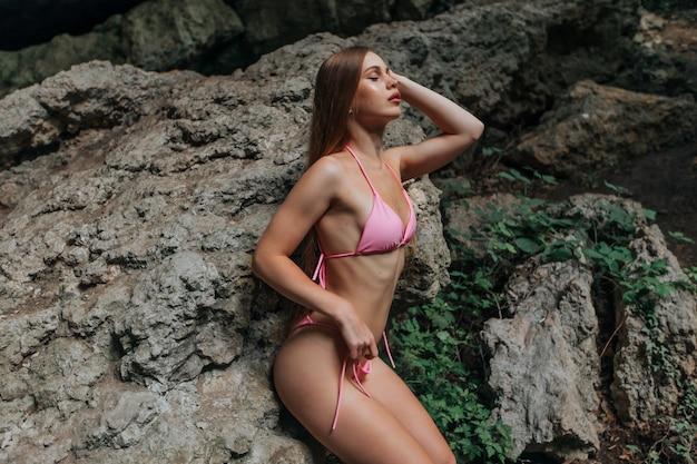 Красивая сексуальная девушка в купальнике лежит на камнях