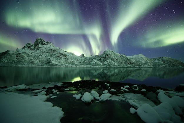 극광 아래 눈 덮인 산의 아름다운 샷