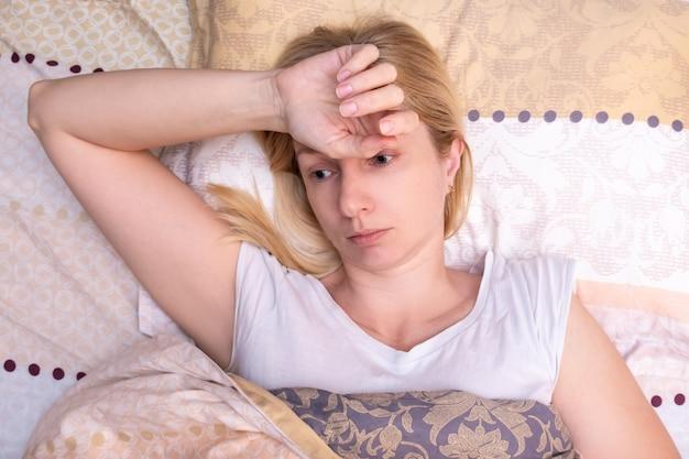 Красивая больная женщина лежит в постели с головной болью, мигренью и страданиями
