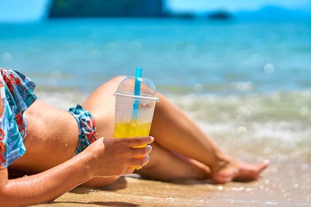 Красивая стройная девушка в купальнике наслаждается загаром, лежа на тропическом пляже, держа в руке стакан ананасового сока.