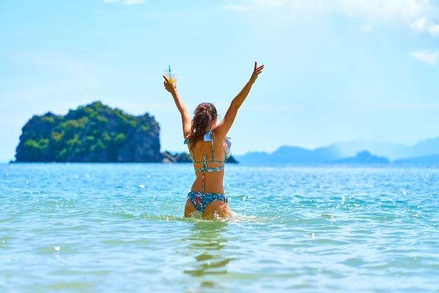 Красивая стройная девушка в купальнике любит танцевать в океане, держа в руке стакан свежего ананаса.