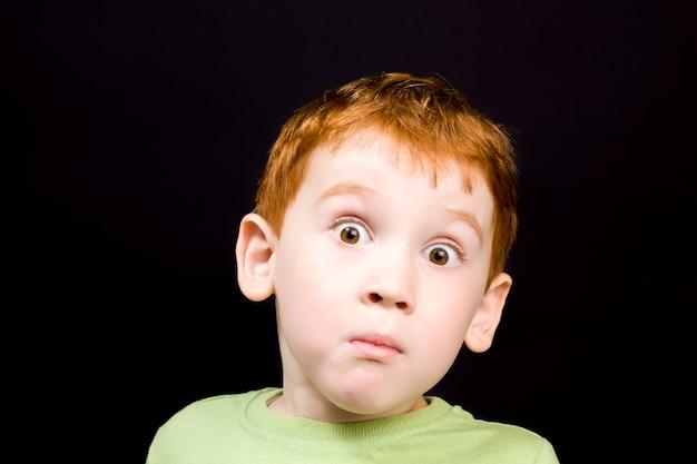 그의 얼굴에 놀라움의 감정을 가진 아름다운 똑똑한 소년, 귀여운 빨간 머리 아이의 클로즈 업 초상화