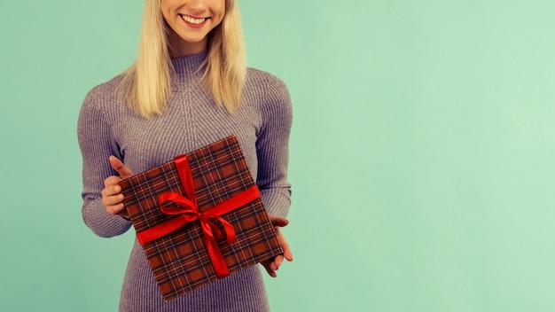 新年の帽子と灰色のドレスを着た美しい笑顔のセクシーな女の子は、贈り物を手に持っています。クリスマスや新年のお祝い