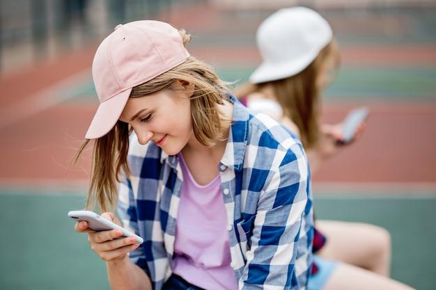Красивая улыбающаяся белокурая девушка в клетчатой рубашке и кепке сидит на спортивном поле