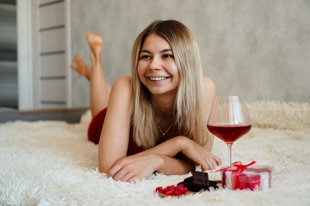 아름 다운 미소 금발 침대에 놓여 있습니다. 발렌타인 데이 아침. 소녀 옆에 와인, 초콜릿, 과자 및 선물 한잔. 사랑에 행복한 아침