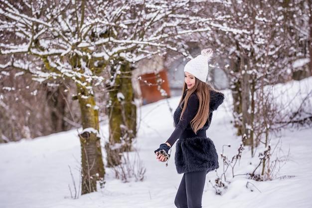 겨울에 검은 옷과 흰 모자에 아름다운 웃는 소녀