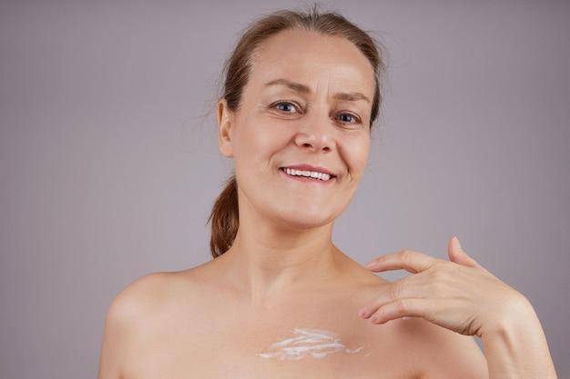 肩がむき出しの美しい笑顔の女性がクリームを肌に塗ります。灰色の壁を越えて。フェイシャルスキンケアのコンセプト。