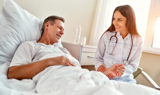 아름다운 웃는 젊은 간호사가 현대 병동의 침대에 누워있는 성숙한 환자의 팔에 맥박을 확인합니다.