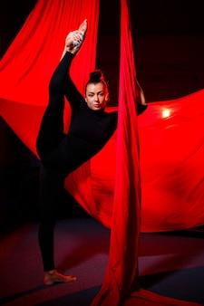 美しいスポーティーな女の子のアクロバットは、赤い絹で体操とサーカスのエクササイズを行います。キャンバス上の空中体操