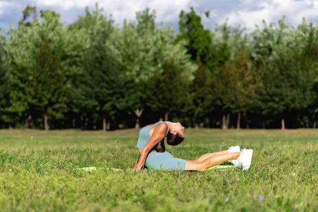 운동복을 입은 아름다운 낚시를 좋아하는 소녀가 도시 공원의 푸른 잔디에서 요가를 연습합니다. 허리 굽힘 포즈의 곡예사, 소녀 체조 강한 유연한 몸
