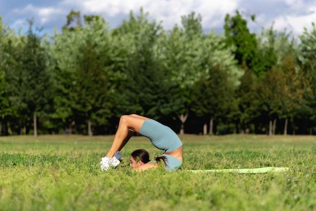 운동복을 입은 아름다운 낚시를 좋아하는 소녀가 도시 공원의 푸른 잔디에서 요가를 연습합니다. 유연한 여성 서커스 체조 선수, 체조 물구나무서기, 손에 서 있는 젊은 곡예사, 요가