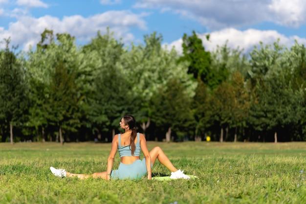 낚시를 좋아하는 아름다운 소녀가 도시 공원의 푸른 잔디에서 요가를 하고 있습니다. 스트레칭. 야외 피트니스 및 생활 균형 개념