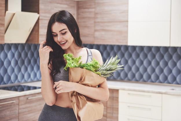 Красивая спортивная женщина со свежими фруктами и овощами на кухне