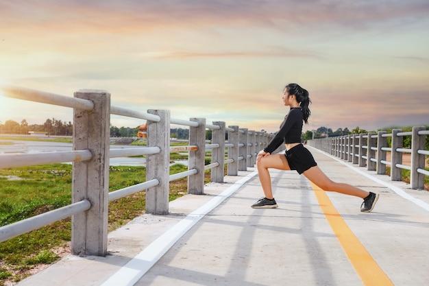 スポーツで湖のほとりを走る美しいスポーティな女性。美しい自然の中で道路を走るスポーティな若い女性。