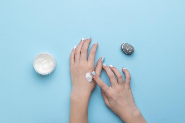Красивый камень, баночка с кремом и женские руки на синем. уход за кожей рук. плоская планировка.