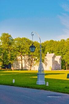 Красивый уличный фонарь на фоне зеленого луга и голубого неба в елагинском парке санкт-петербурга