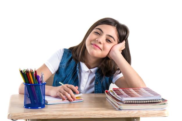 Красивая студентка сидит за партой и пишет письмо уайт