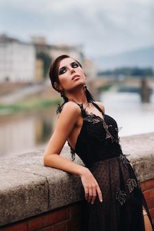 검은 드레스를 입은 아름답고 세련된 신부가 이탈리아의 구시 가지에있는 검은 드레스를 입은 모델 피렌체를 산책합니다.