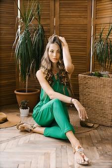 熱帯植物の近くに座っている長い髪とプロのメイクで緑のジャンプスーツで美しいスタイリッシュな白人少女