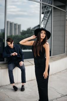 黒い服とメガネを身に着けた美しくスタイリッシュな若者たちが、オフィスビルの夕日を背景に立ちます。ファッションとスタイル