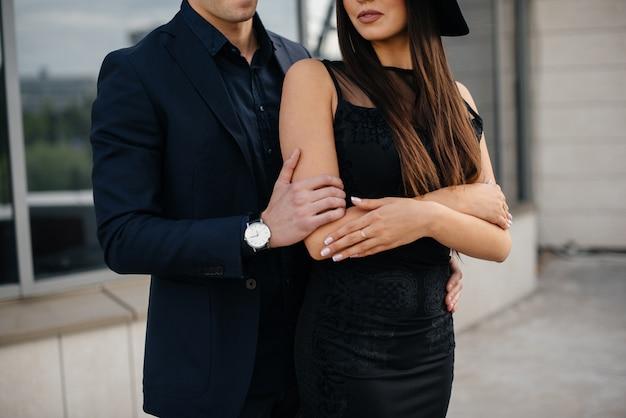 Красивая, стильная пара молодых людей в черной одежде и очках стоит на фоне офисного здания на закате. мода и стиль