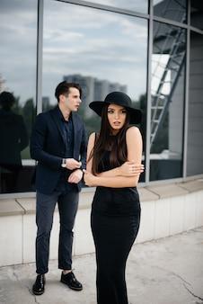 黒い服と眼鏡をかけた美しくスタイリッシュな若者のペアが、日没のオフィスビルの隣に立ちます。ファッションとスタイル。