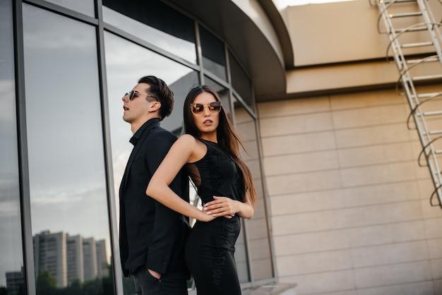 黒い服とメガネを身に着けた美しくスタイリッシュな若者たちがオフィスビルの上に立つ夕日。ファッションとスタイル