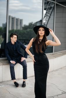 Красивая, стильная пара молодых людей в черной одежде и очках стоит