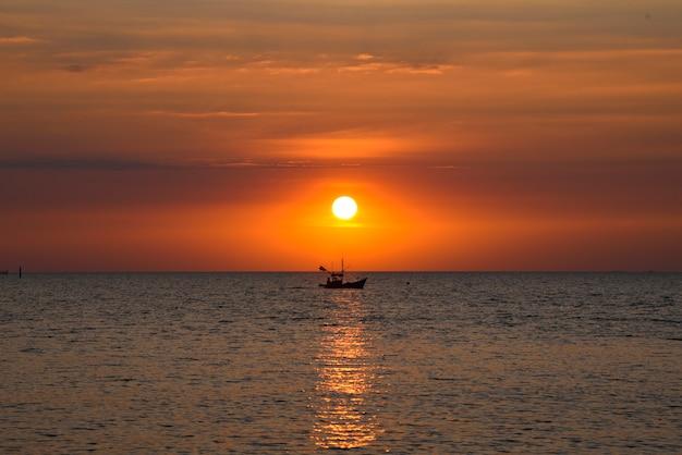 夕方の美しい夕日タイのバンセーンビーチを漁師の船が通り過ぎました。