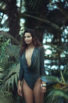 이국적인 사이에서 정글에 서있는 자연스러운 메이크업과 젖은 머리카락을 가진 아름다운 그을린 소녀