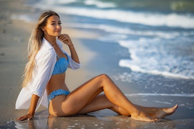 Красивая загорелая стройная девушка в голубоватом купальнике и белоснежной рубашке сидит у кромки морской воды и вглядывается в горизонт теплым солнечным летним днем.
